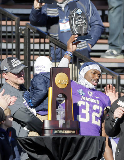 James Madison head coach Mike Houston, left, watches as running back Khalid Abdullah (32) holds up the most valuable player award after their 28-14 win over Youngstown State in the FCS championship NCAA college football game, Saturday, Jan. 7, 2017, in Frisco, Texas. (AP Photo/Tony Gutierrez)