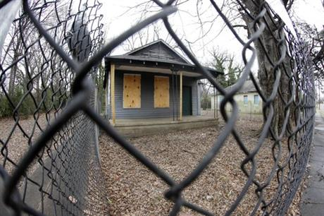 In this Jan. 16, 2017, file photo, the abandoned childhood home of singer Aretha Franklin sits behind a security fence in Memphis, Tenn. Recently, the Franklin birthplace and the surrounding neighborhoods have moved to the forefront of a large cleanup effort, as the city refuses to accept decay as a fact of life in the urban landscape. (AP Photo/Mark Humphrey, File)