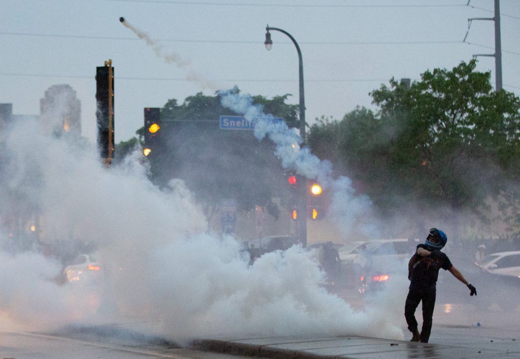 A protester throws a gas canister back at police during a protest over the killing of George Floyd in Minneapolis on May 26, 2020. (Chris Juhn/Zenger)
