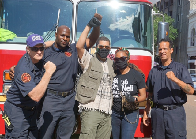 Mayor Chokwe Antar Lumumba and First Lady Ebony Lumumba pictured with firefighters in solidarity