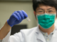 University of Cincinatti researcher Tianyu Zhang holds a vial of grapheme used as a catalyst to convert carbon dioxide to methane. (Andrew Highley, U. Cincinatti)