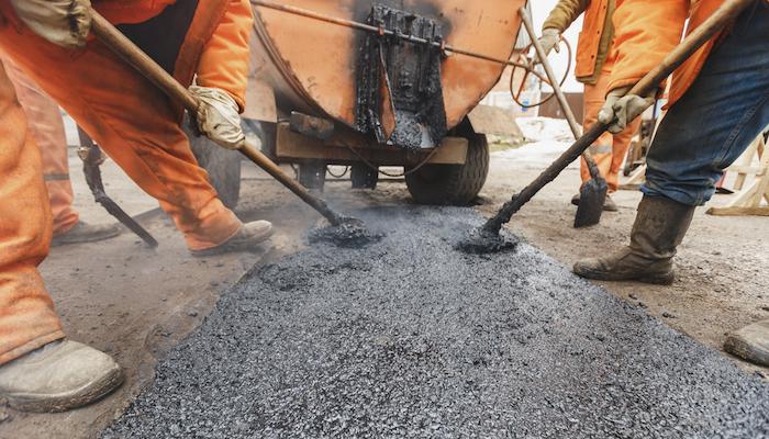 Workers repairing the road with shovels fill asphalt driveway repair