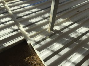 Universal grooved R-Floor system on packed sand replaces standard basement poured floor