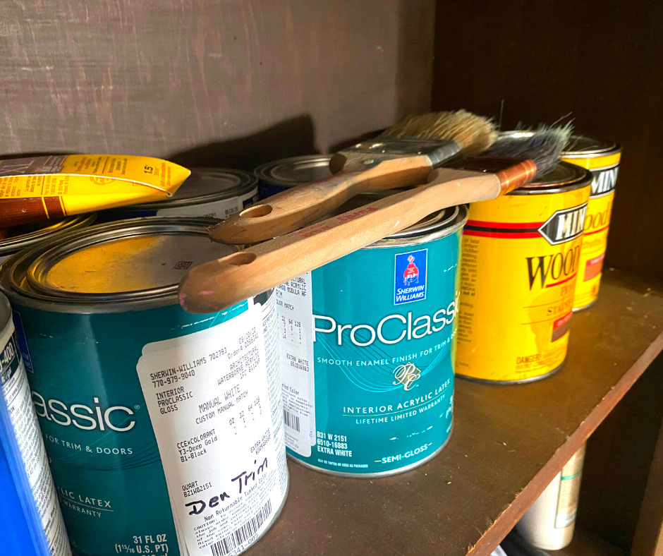 cans of old paint on a brown shelf