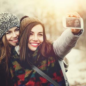 Two teenage girls taking a selfie outdoors in winter