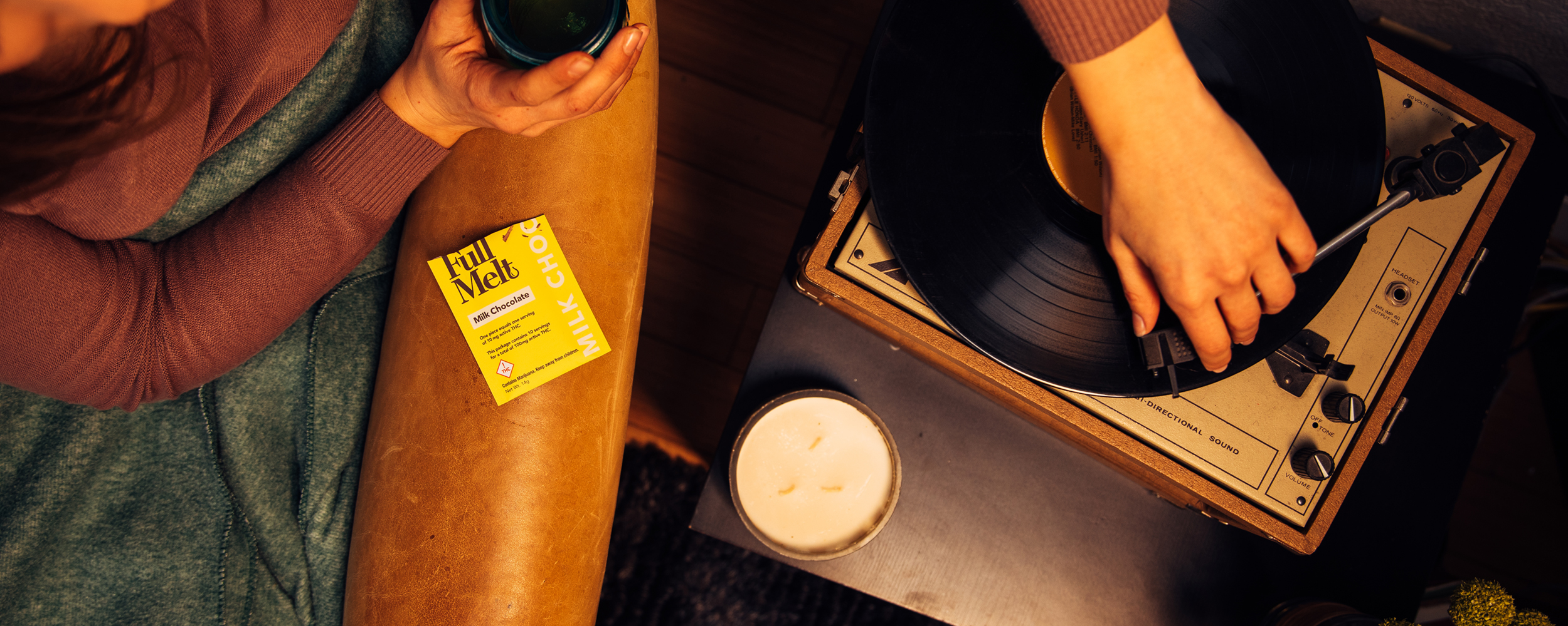 Woman playing a record, drinking coffee, and enjoying Full Melt infused chocolate on a leather couch