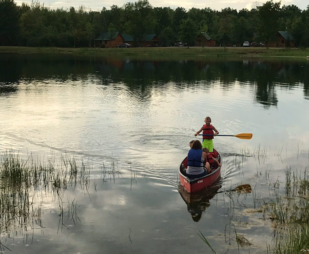 children canoeing on the pond at Branches of Niagara campground
