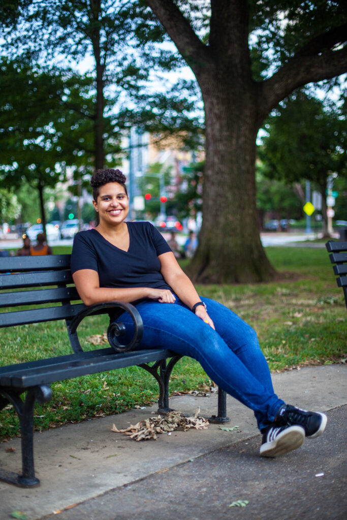 Rehana wearing a black shirt and jeans sitting on a bench in Logan Circle. She is smiling at the camera.