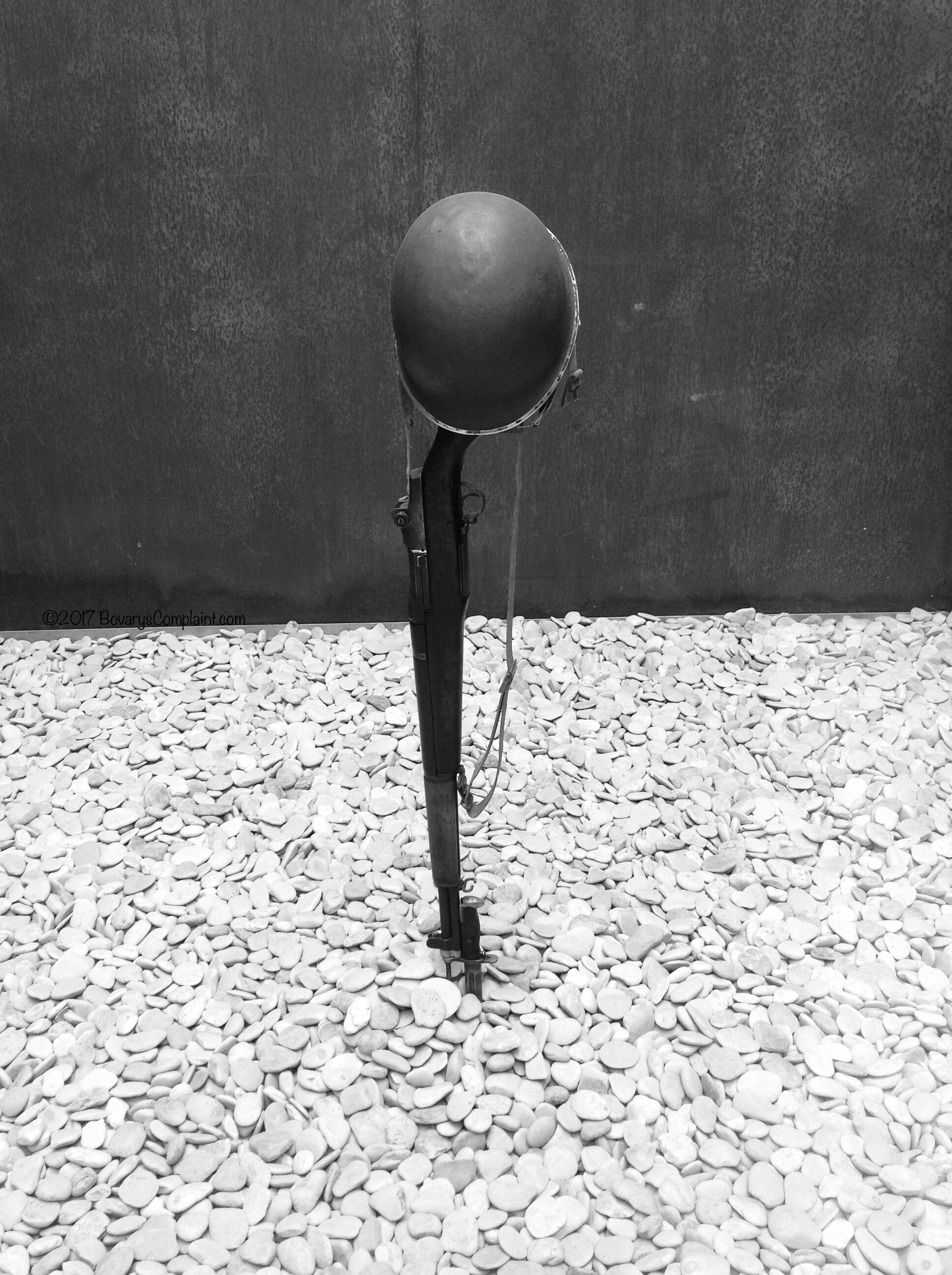 Black and White photo of World War 2 Army hat mounted on gun from Normandy, France.