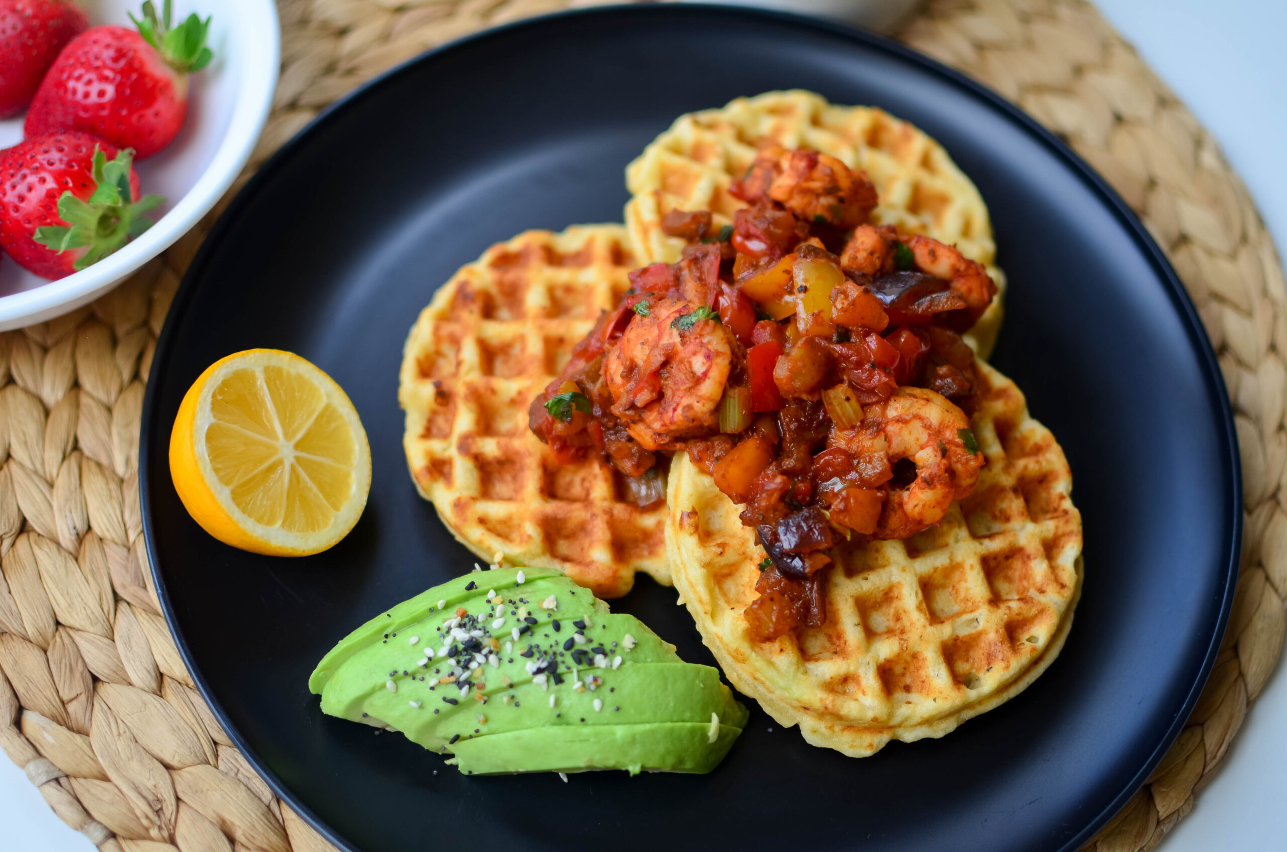 a delicious plate of Cassava corn waffles and shrimp creole with a side of avocado