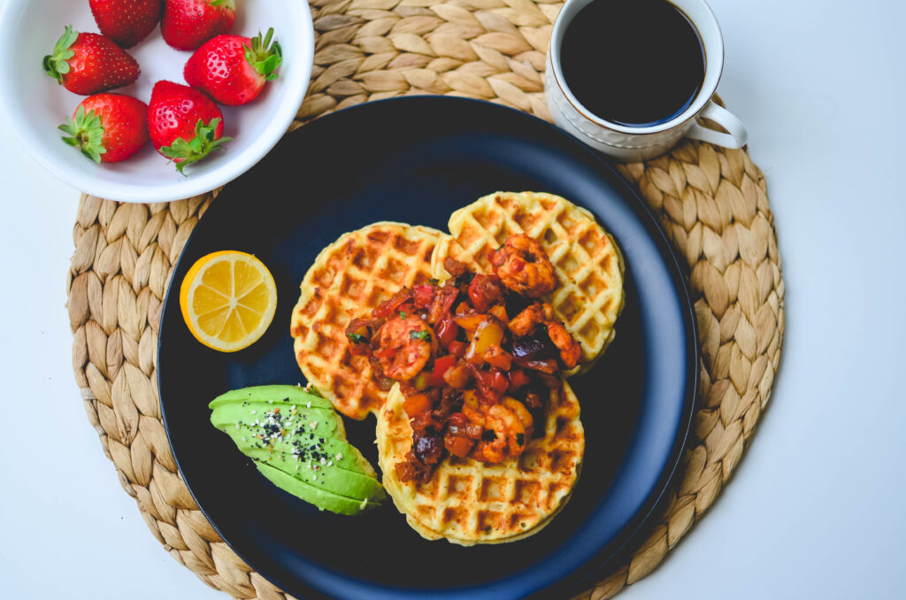 A overhead shot of cassava corn waffles with avocado, shrimp creole with fruit and coffee