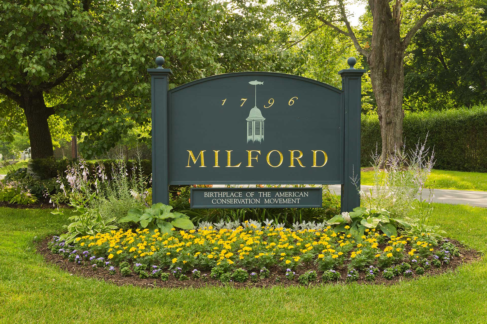 town entrance sign of milford pa surrounded by a garden