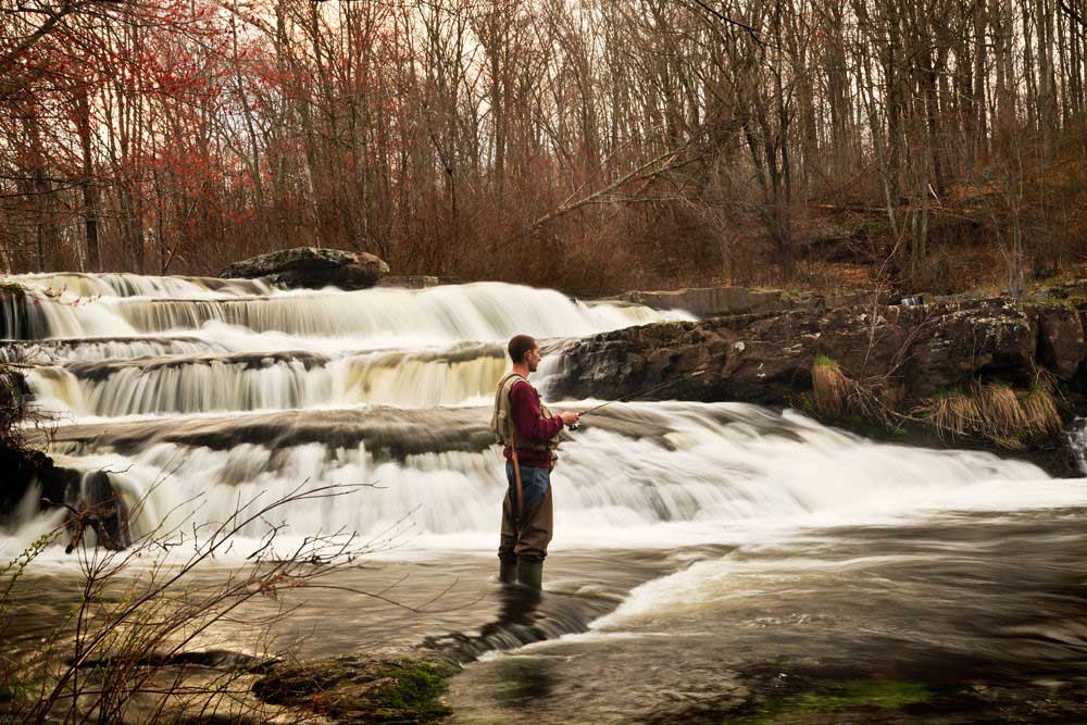 man in waders and fishing vest standing next to waterfalls fishing
