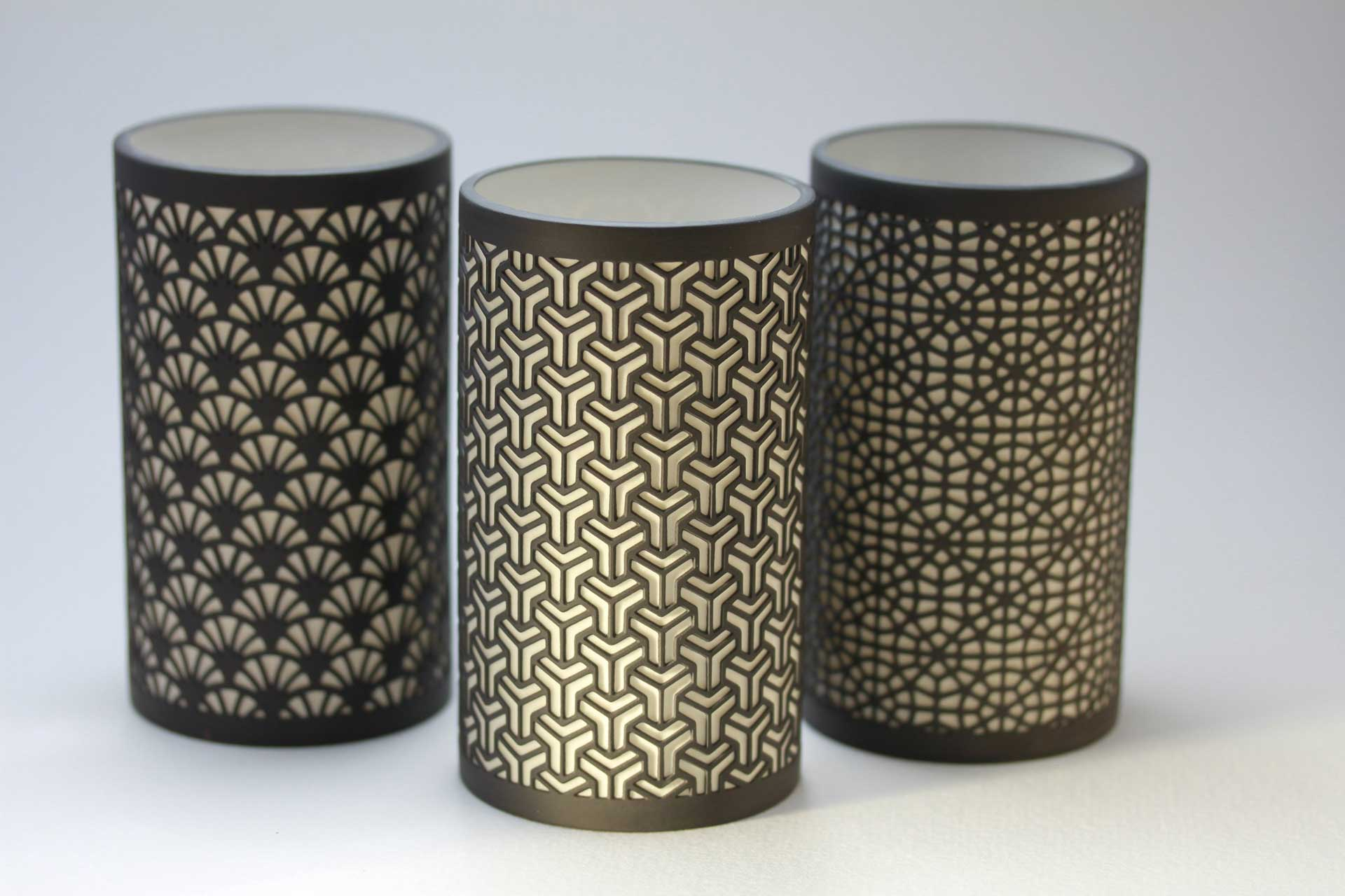 geometric patterned home decor cylinders on a white background
