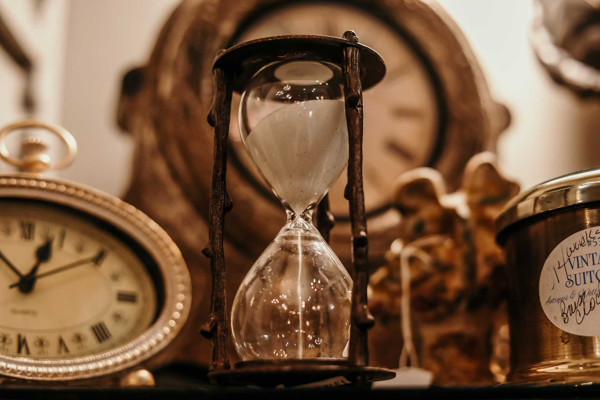 antique sand hour glass with vintage clocks