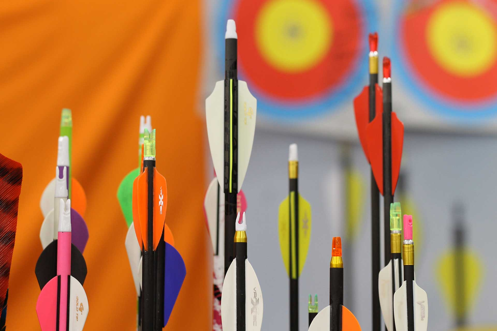 close up of different colored ends of archery arrows