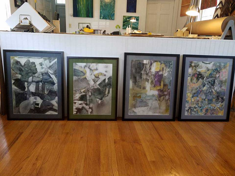 a desk at beveled edge showing four pieces of abstract art with custom mats and frames