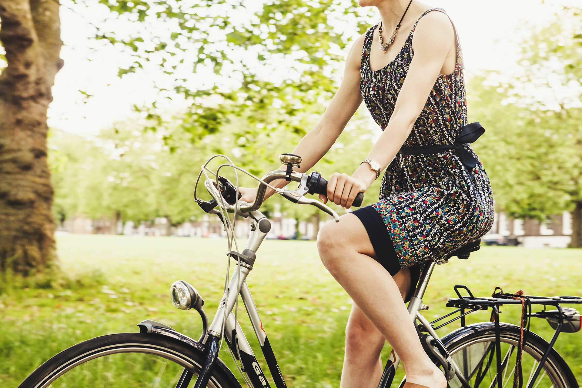 a woman in a flowery dress riding a cruiser bicycle in nature