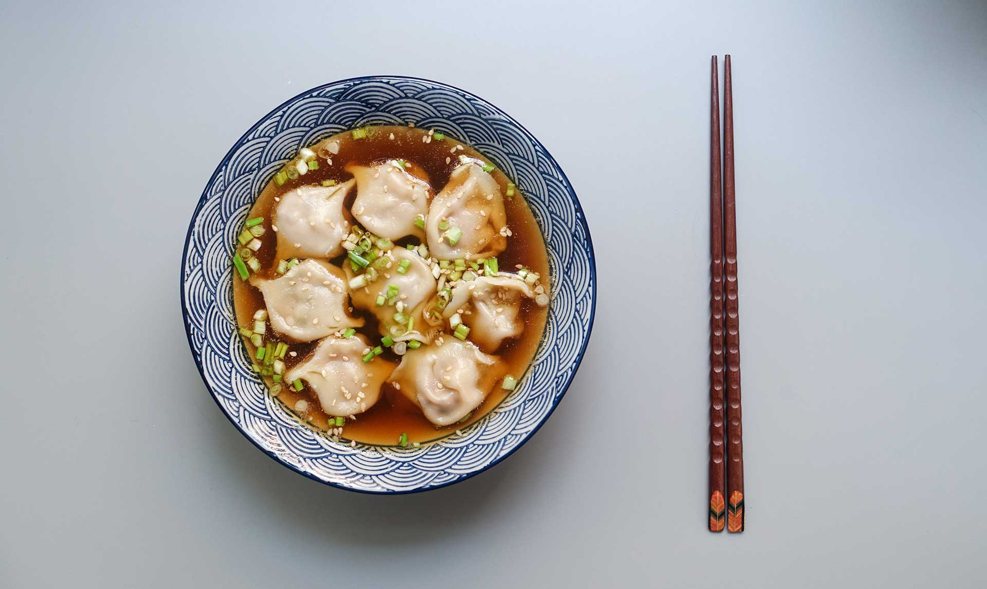 chinese dumplings in a bowl with wooden chopsticks next to it