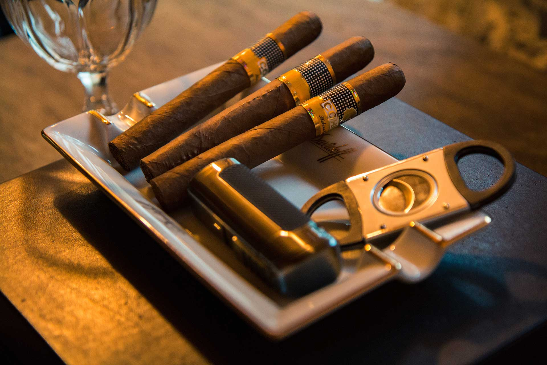 a cigar tray with three cigars and a cigar cutter