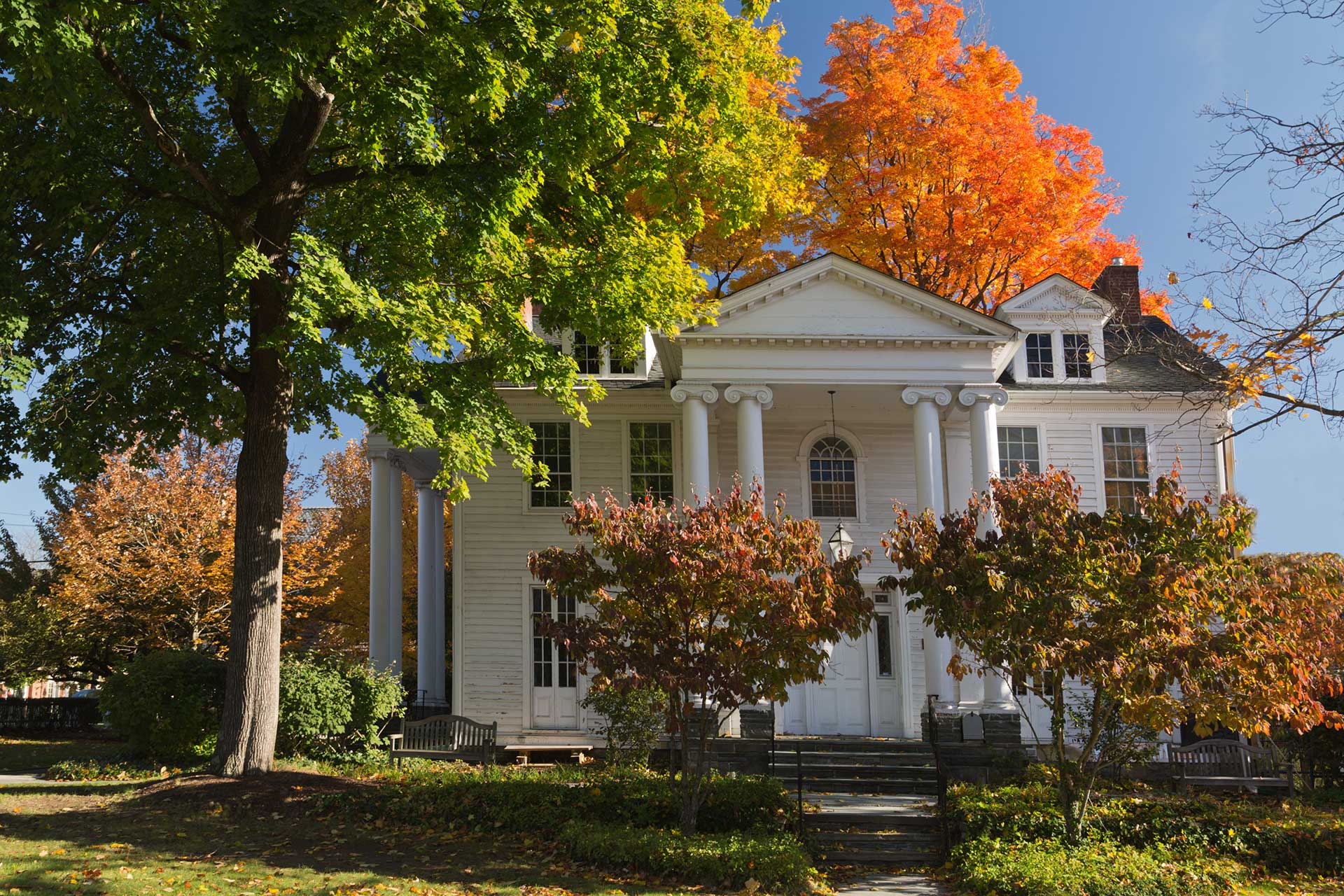 the large white community house surrounded by fall trees