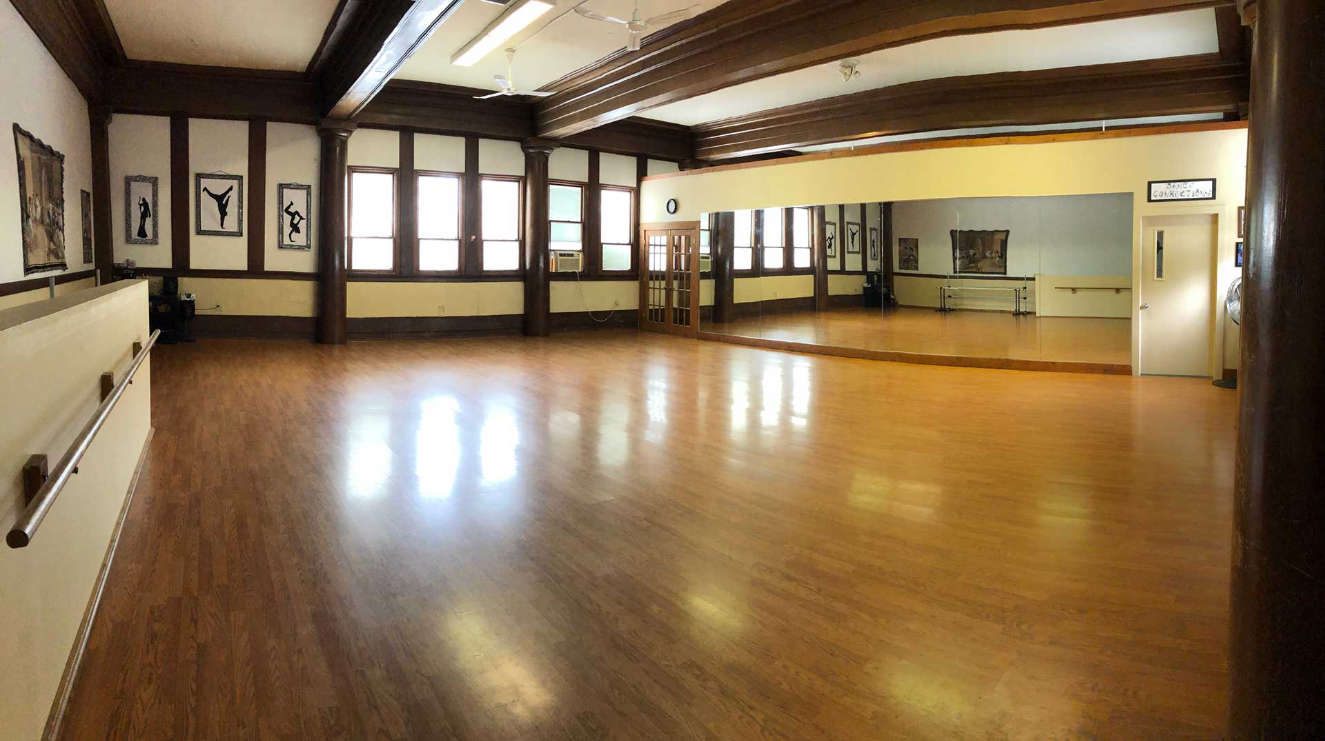 empty dance studio room with wood floors and wall of mirrors