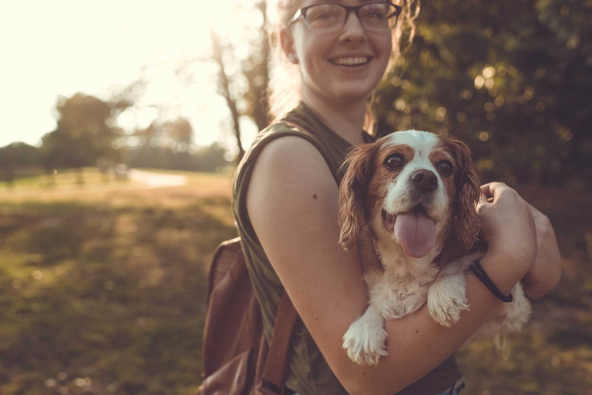 woman in a tank top holding a white and brown dog in her arms outside and smiling
