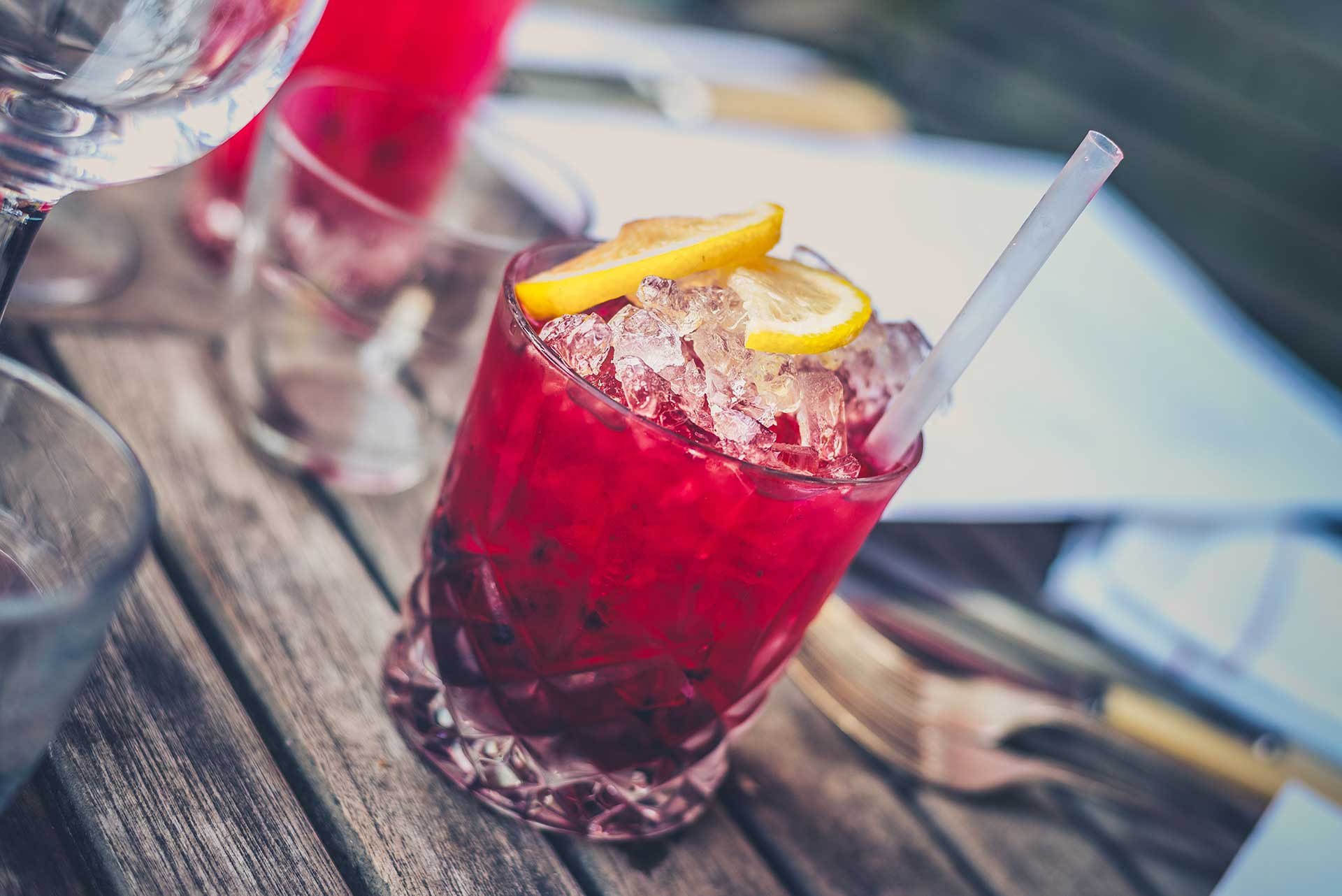 a red seasonal cocktail with lemon wedges at jive bar and lounge