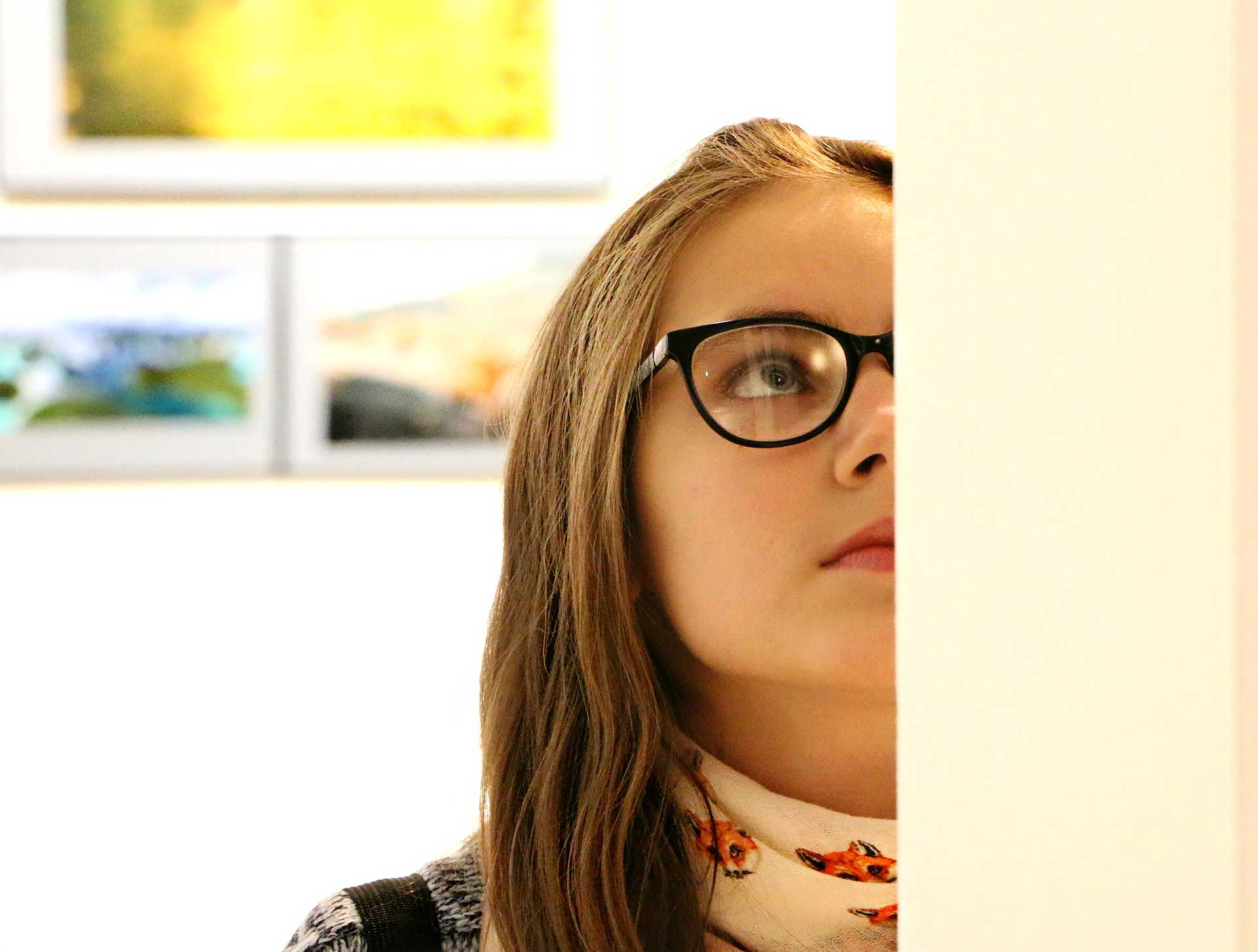 a girl with glasses looking up at the wall of an art gallery