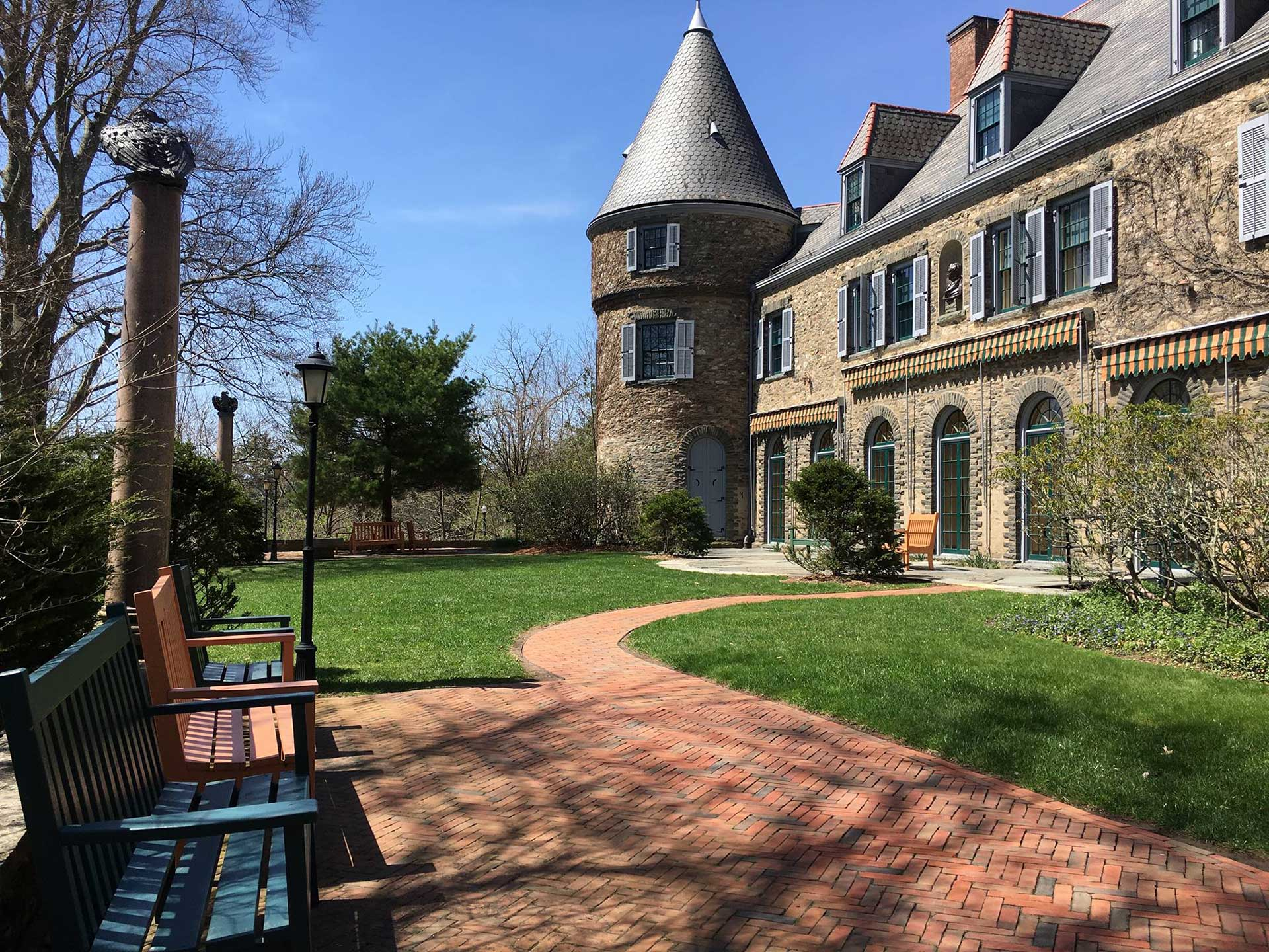 the outside of grey towers with a brick sidewalk and benches