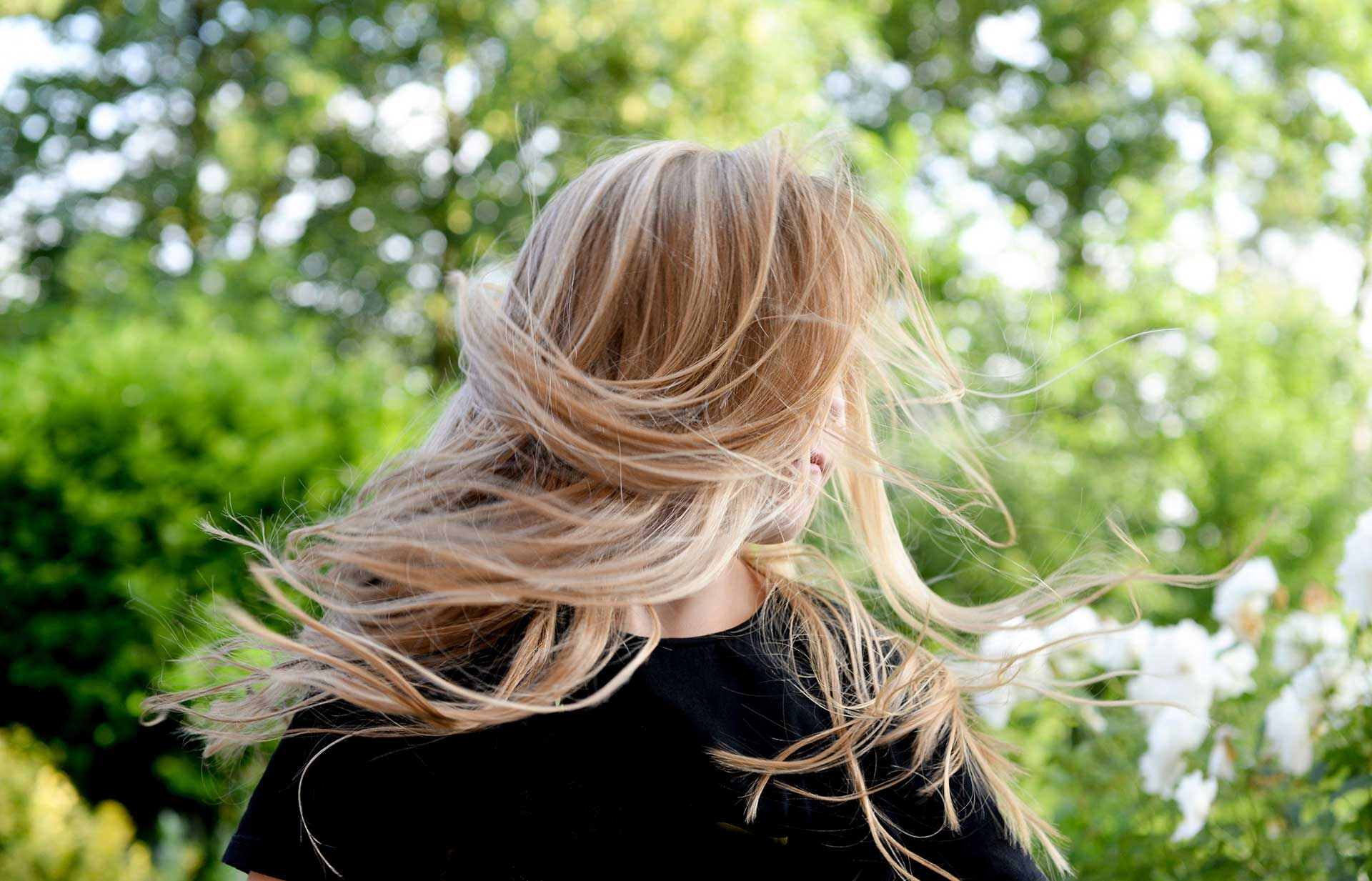 blonde hair blowing around the face of a girl who is outside
