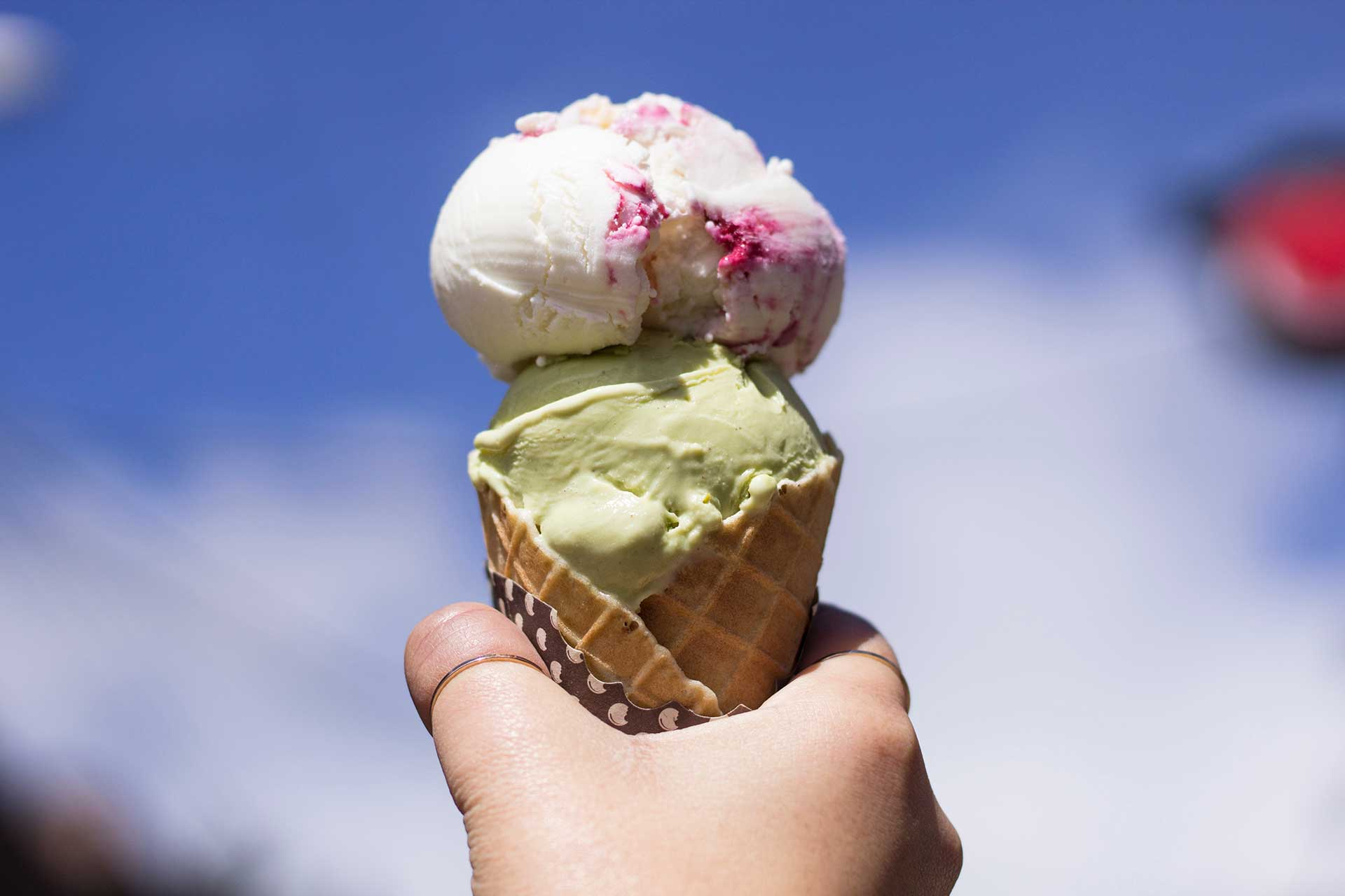 a hand holding a waffle cone with a scoop of pink and a scoop of green ice cream