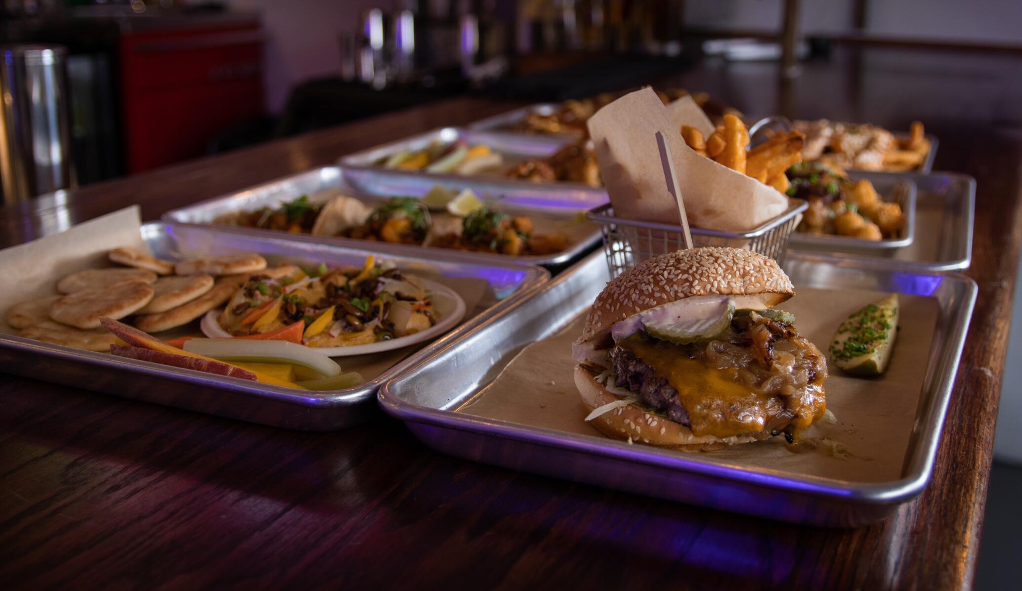 plates of food at a bar including a burger