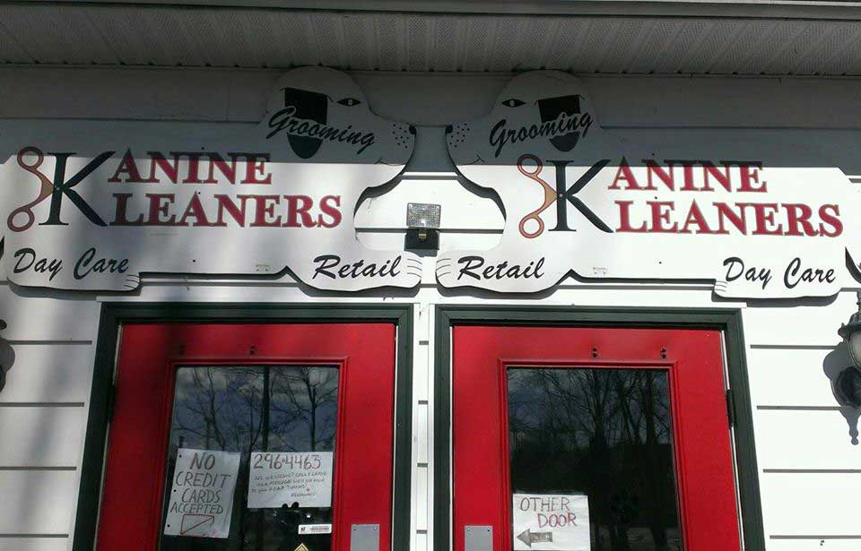 two dog shaped signs for kanine kleaners hung over their red entry doors