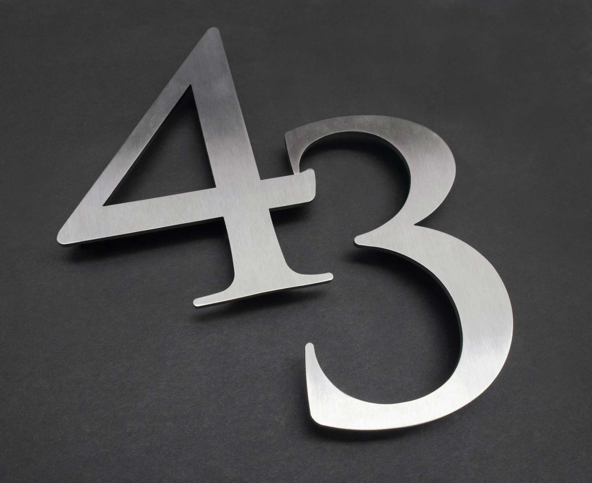 the number 43 laser cut in metal on a grey background