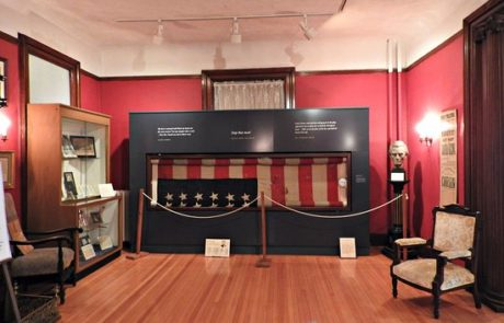 a room of a historical museum displaying the lincoln flag behind a roped off section