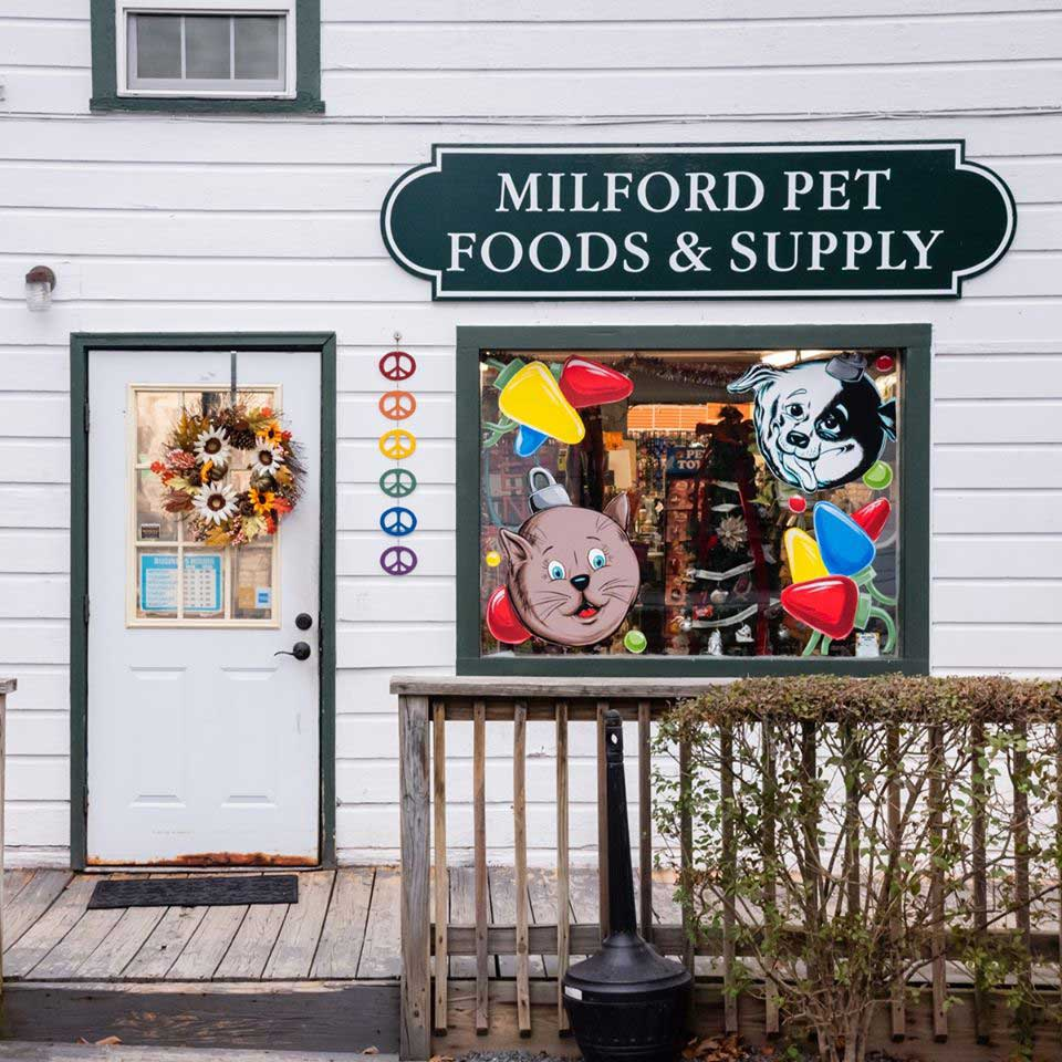 the outside entrance of milford pet foods and supply with art in the window