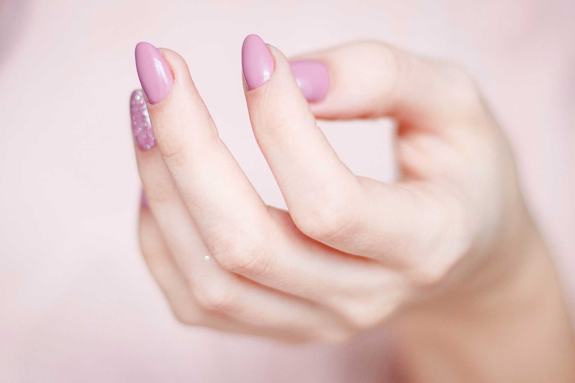 close-up of hand with manicure and pink nails from happy nails