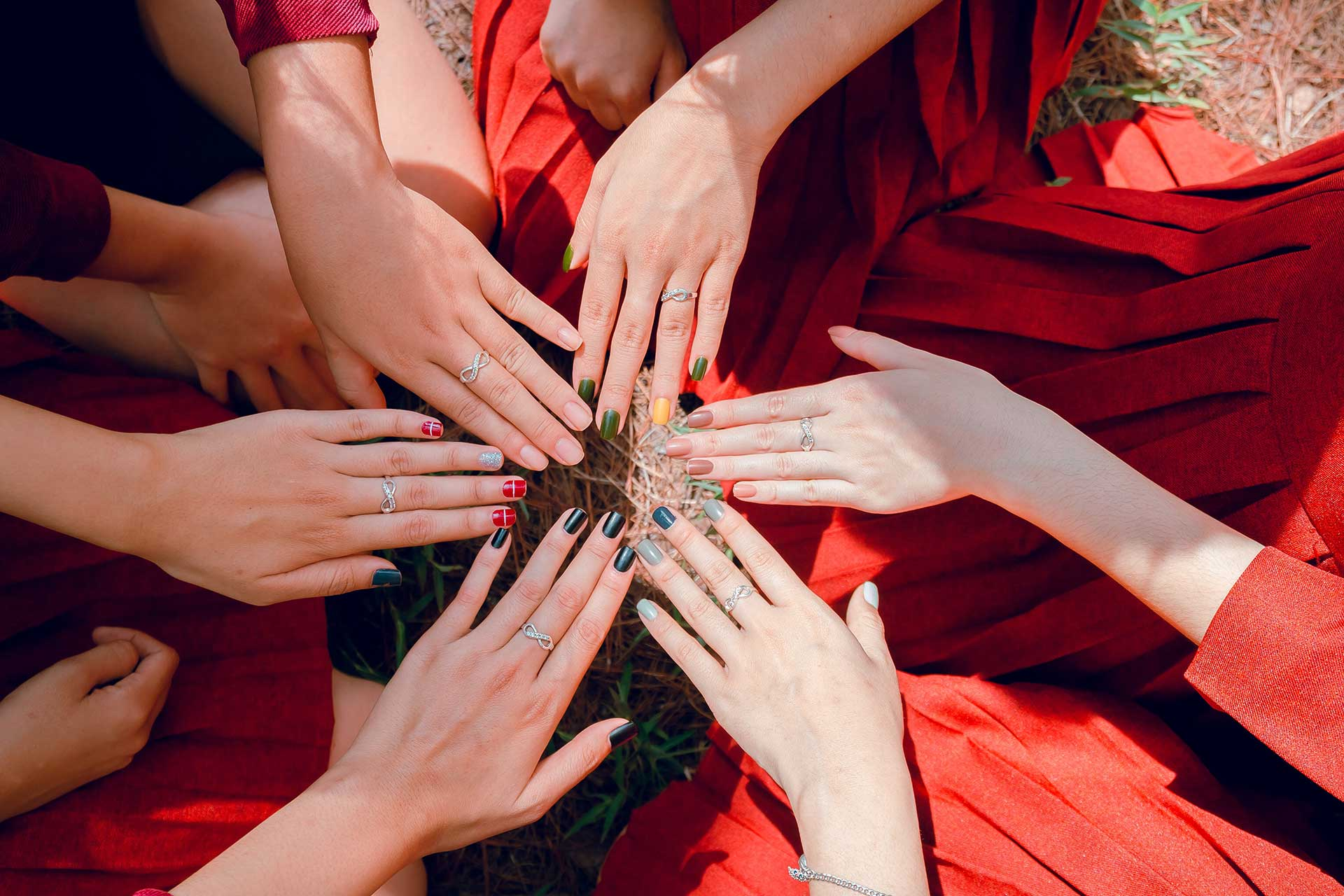 women sitting in a circle with one hand in each showing their different manicures