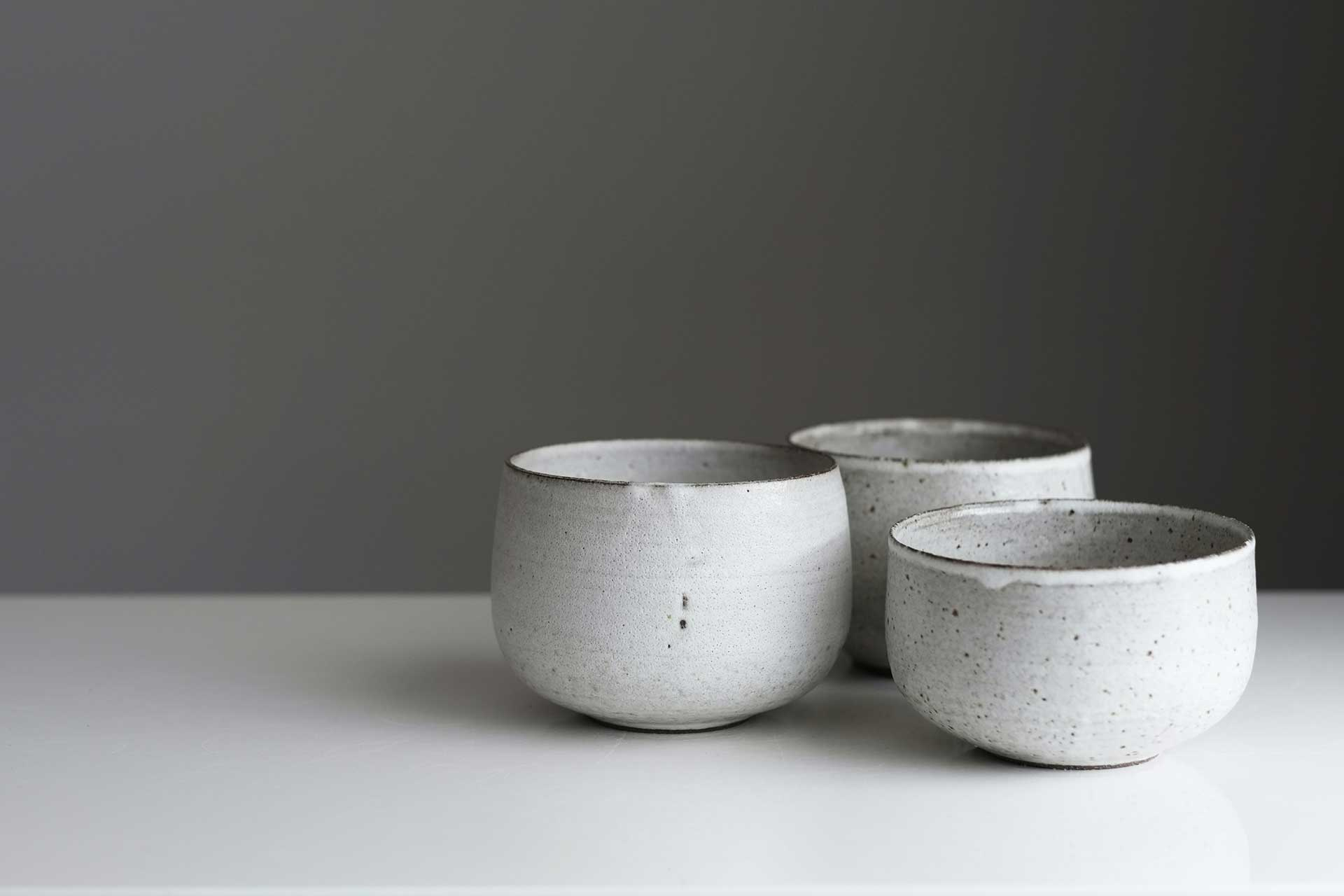 three gray speckled ceramic bowls on a table