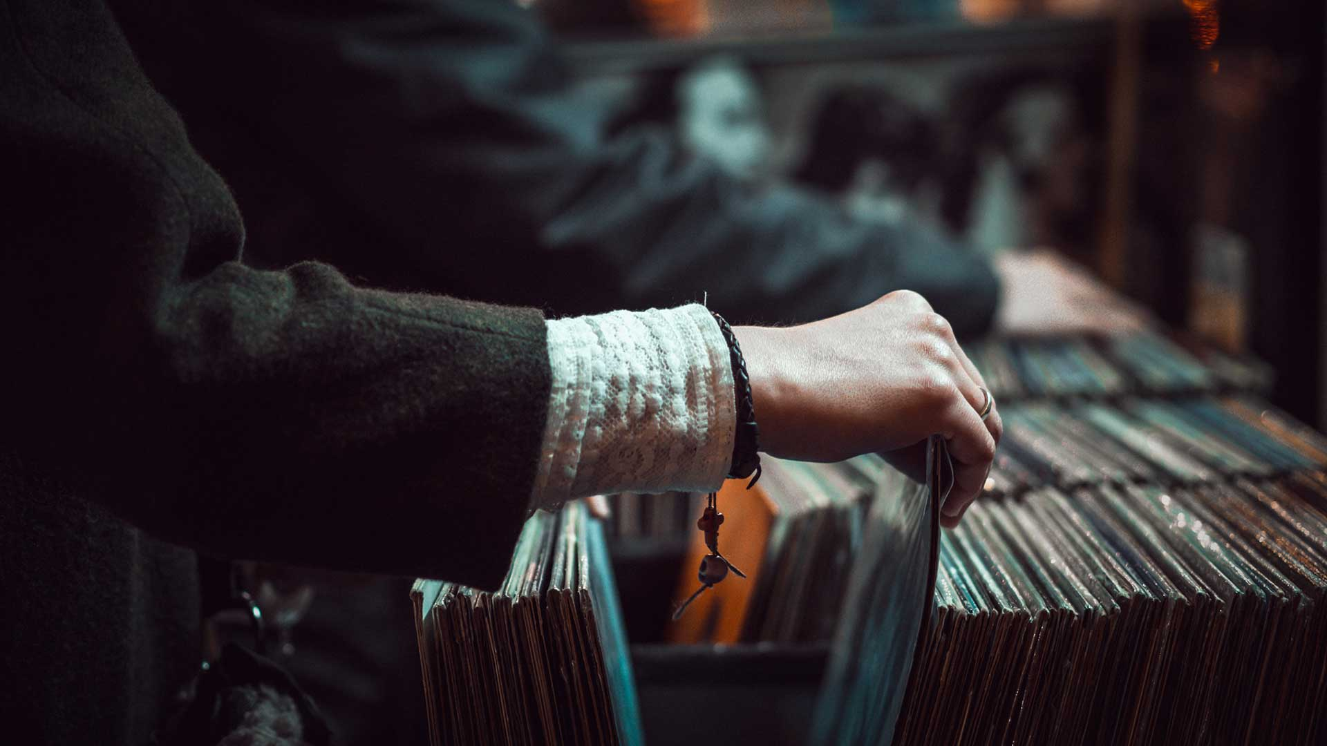 a hand browsing through records for sale