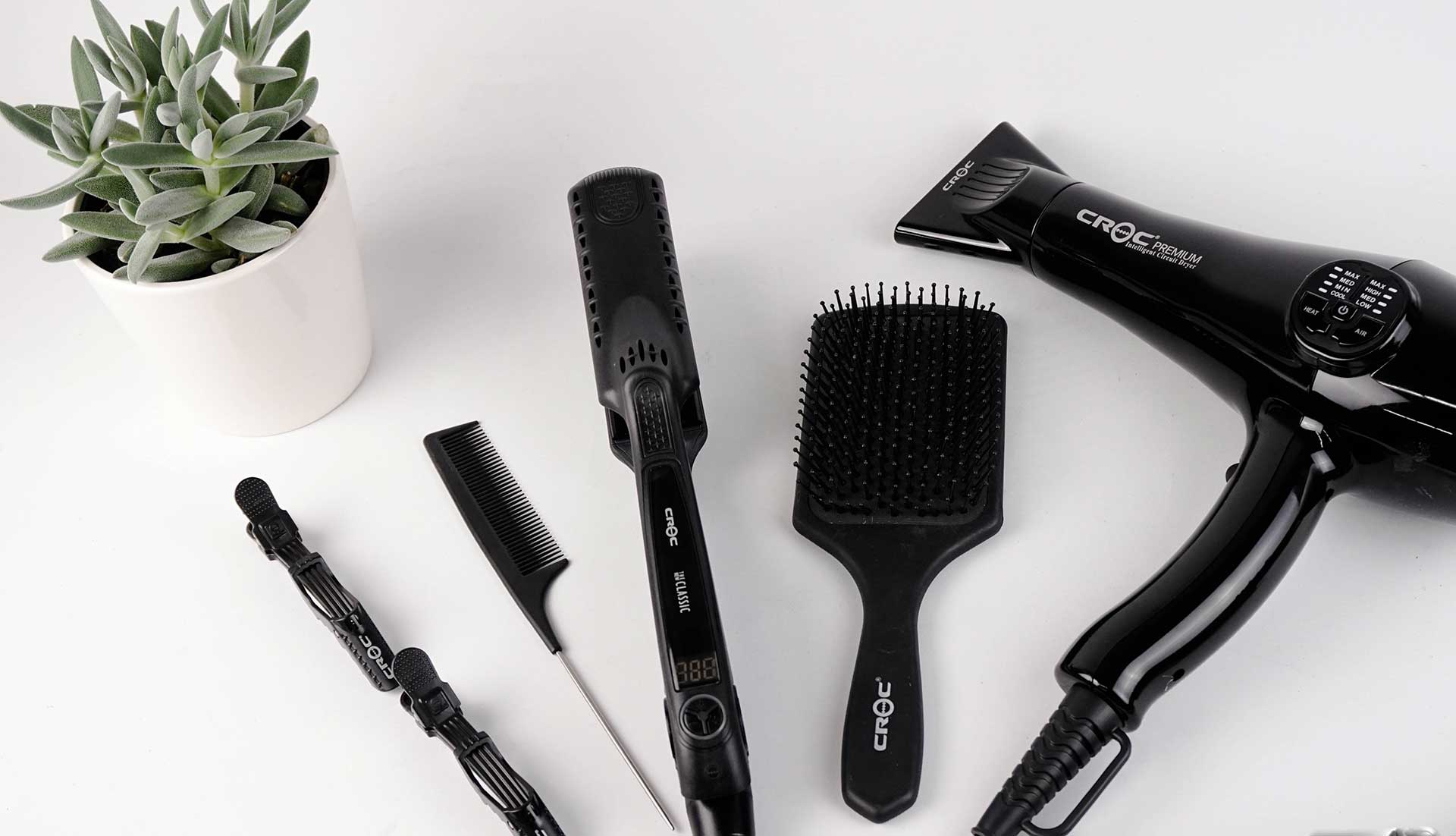 hair styling tools on a white background with a small succulent plant