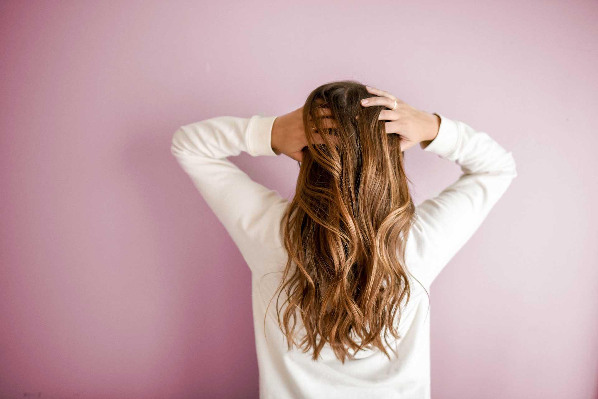 woman running her hands through her long hair facing away
