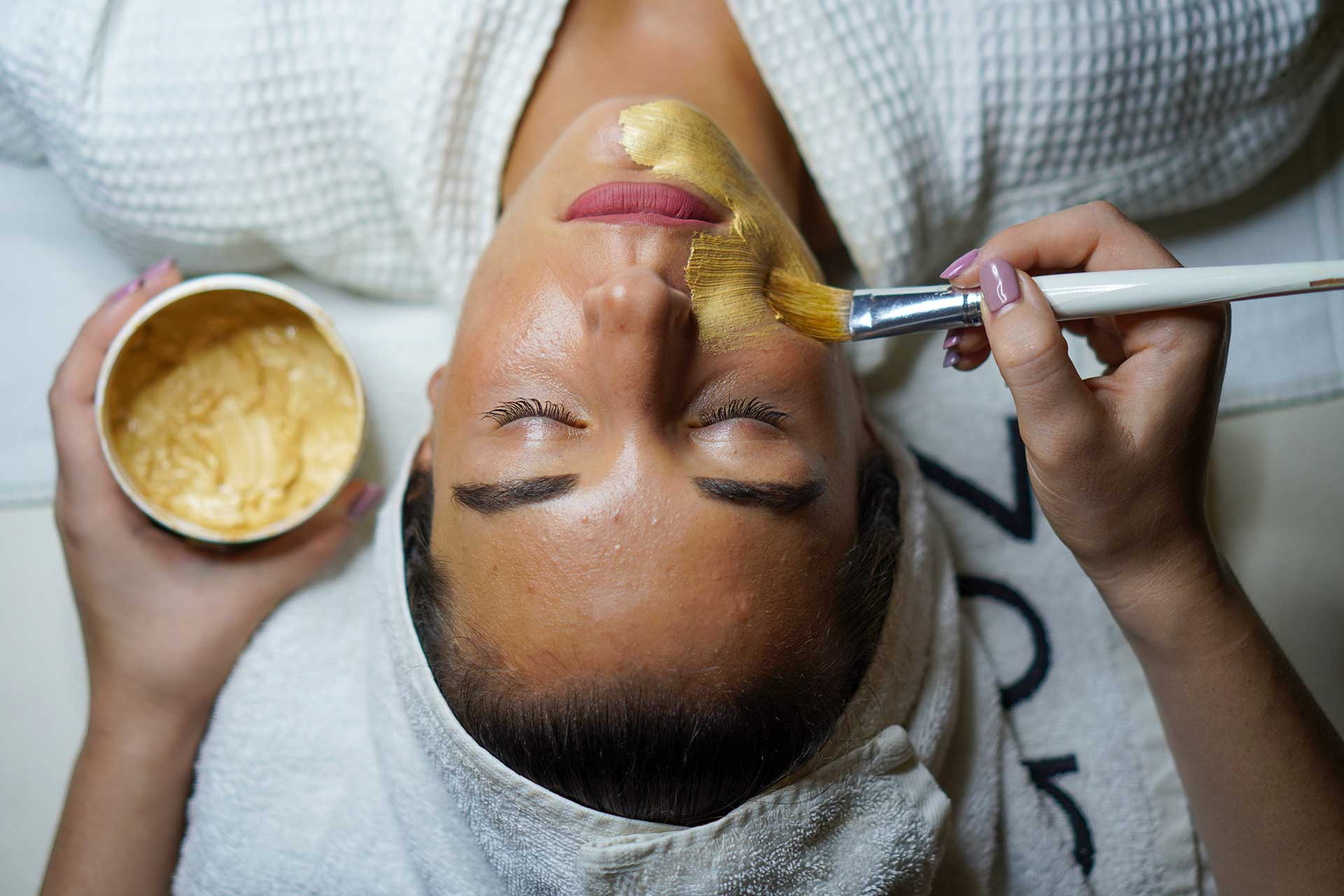 woman with her eyes closed receiving a gold facial treatment at Badea & Soul Day Spa