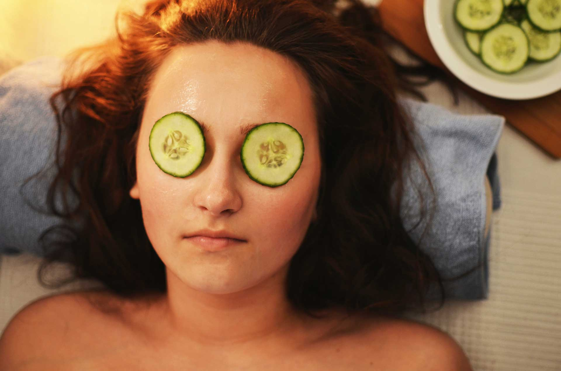 face of woman laying down with cucumber slices over her eyes at tlc salon and spa