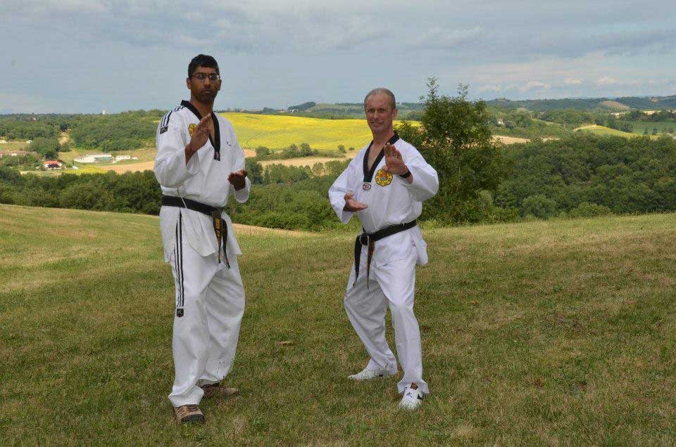 two TPM martial art trainers in a green outdoor environment in Taekwondo poses