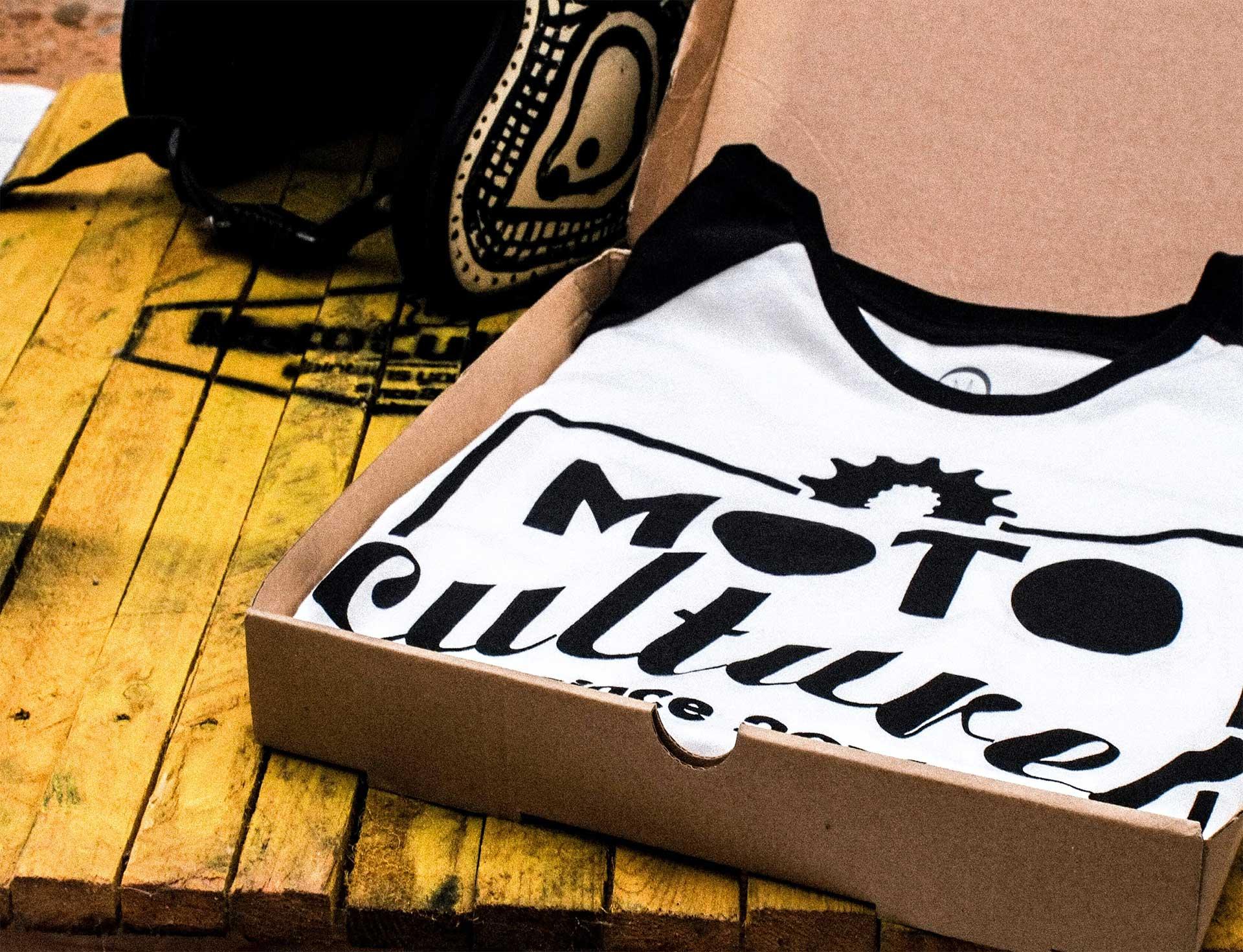 a black and white raglan shirt with a custom screenprint folded inside of a box