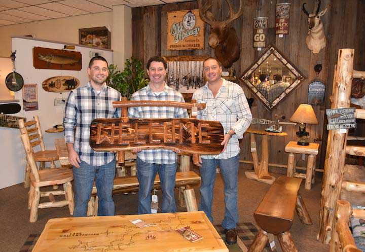 three workers in van gorders furniture holding a wooden welcome sign