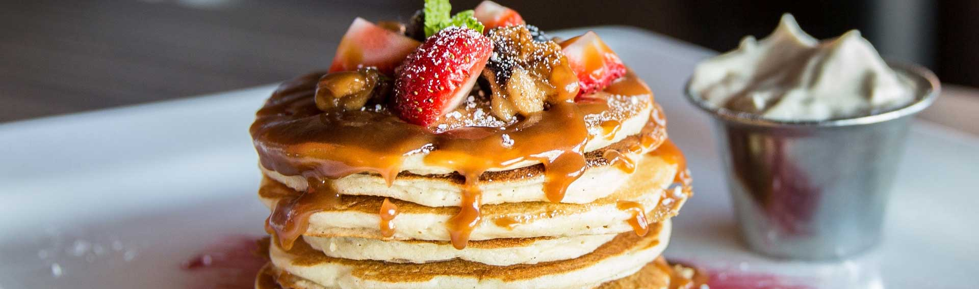 a stack of diner pancakes with syrup and berries and whipped butter on the side