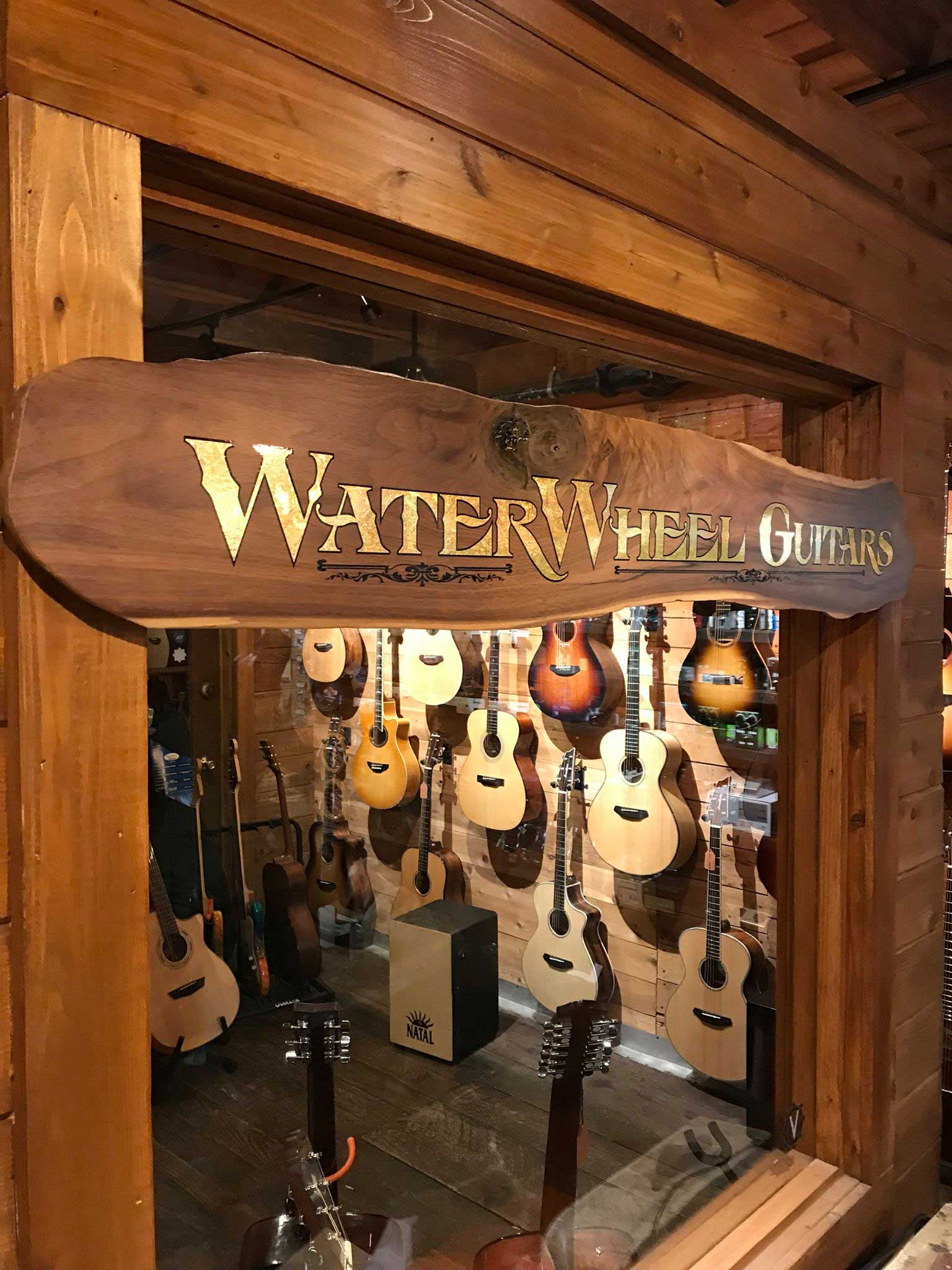 water wheel guitar sign in a window with guitars hanging on a wall behind it
